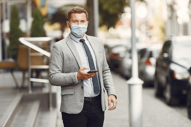 Hombre de negocios en una ciudad. persona con máscara. chico con teléfono.