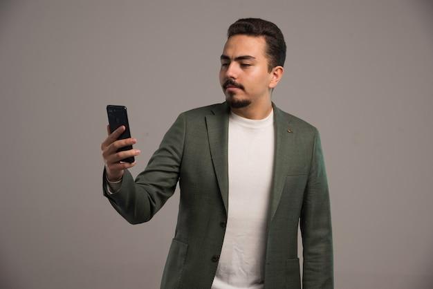Un hombre de negocios en código de vestimenta revisando su teléfono.