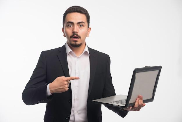 Un hombre de negocios en código de vestimenta sosteniendo una computadora portátil y apuntando a ella.