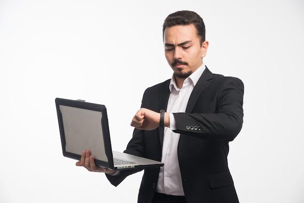 Un hombre de negocios en código de vestimenta sosteniendo una computadora portátil y controlando su tiempo.