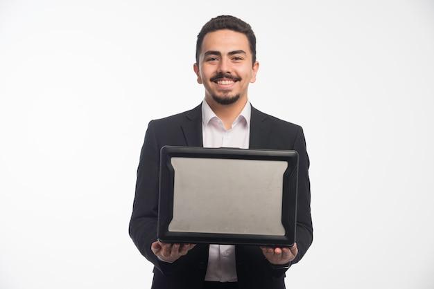 Un hombre de negocios en código de vestimenta sosteniendo una computadora portátil.
