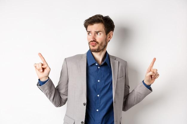 Hombre de negocios complicado apuntando en dos direcciones, preocupado por elegir, mirando a un lado y pensando, tomando decisiones, de pie sobre un fondo blanco en traje.