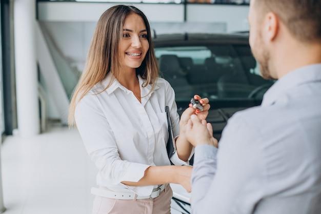 Hombre de negocios comprando un coche nuevo en una sala de exposición de coches