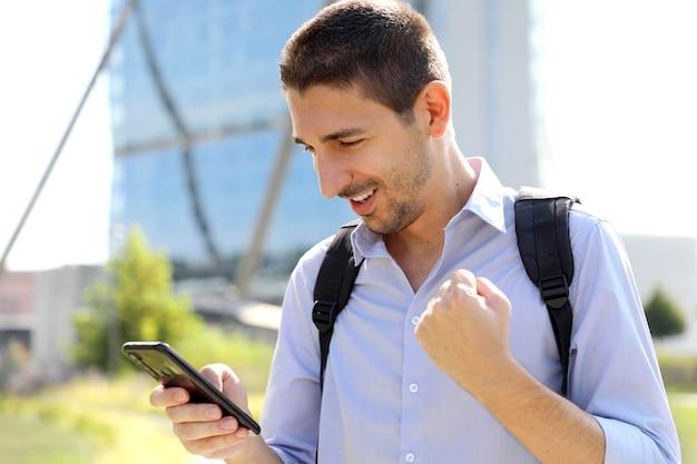 Hombre de negocios comprobando buenas noticias en smartphone