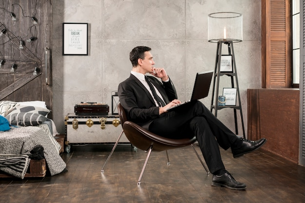 Hombre de negocios con la computadora portátil que mira lejos y que piensa