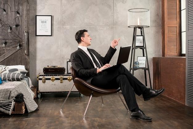 Hombre de negocios con la computadora portátil que señala lejos y que reflexiona
