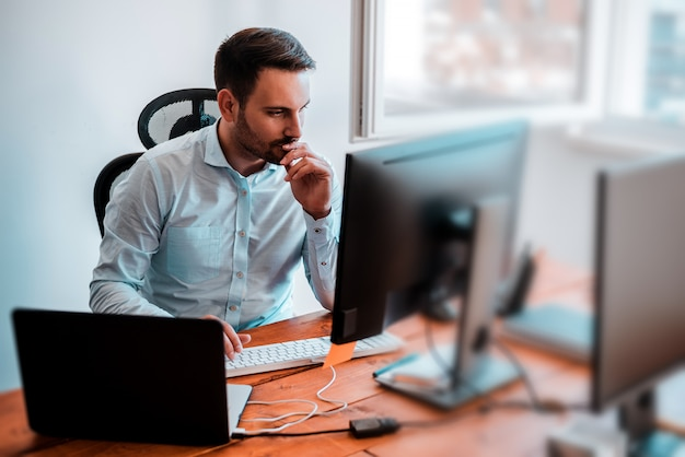Hombre de negocios concentrado que analiza gráficos en su oficina en la computadora.
