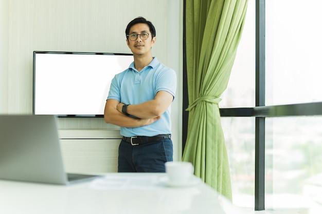 Hombre de negocios confiado con los brazos cruzados contra la pantalla en una oficina.