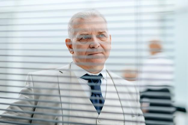 Hombre de negocios confiado empujando persianas de ventana abierta previsión y perspectiva