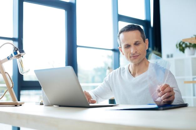 Hombre de negocios confiado. hombre agradable agradable serio sentado en la mesa y usando una computadora portátil mientras trabaja en su oficina