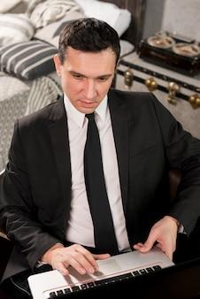Hombre de negocios confiado joven que trabaja en el ordenador portátil