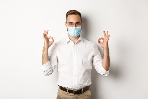Hombre de negocios confiado con máscara médica y mostrando signos de aprobación, fondo blanco.