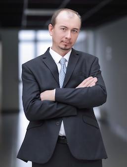 Hombre de negocios confiado de pie en el pasillo de la oficina.