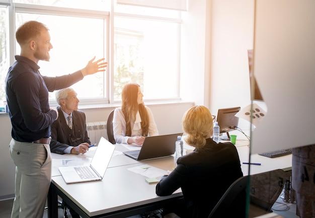 Hombre de negocios confiado que da presentación a su colega en la reunión