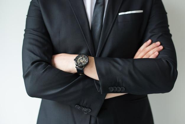 Hombre de negocios confiado que presenta con los brazos cruzados