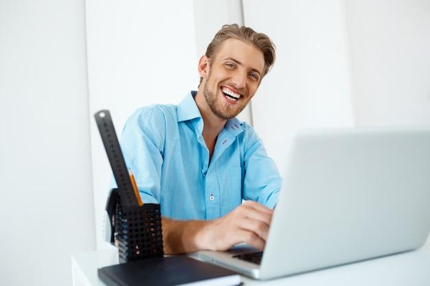 Hombre de negocios confidente alegre hermoso joven que se sienta en la tabla que trabaja en la computadora portátil con la taza de café a un lado. sonriente. interior de oficina moderno blanco