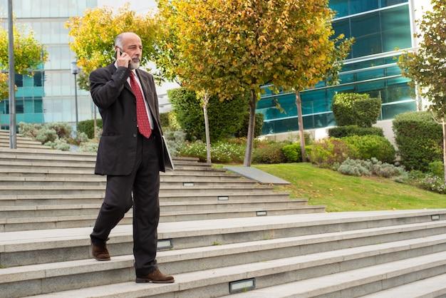 Hombre de negocios confidente con dispositivos caminando sobre pasos