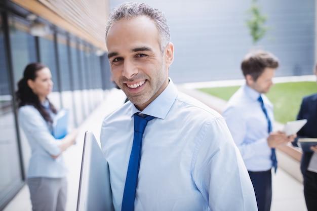 Hombre de negocios confidente que sonríe fuera del edificio de oficinas