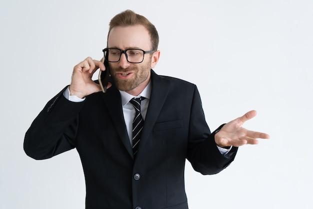 Hombre de negocios confuso en chaqueta negra que habla en el teléfono