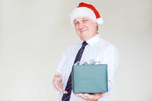 Hombre de negocios contento en santa hat giving gift