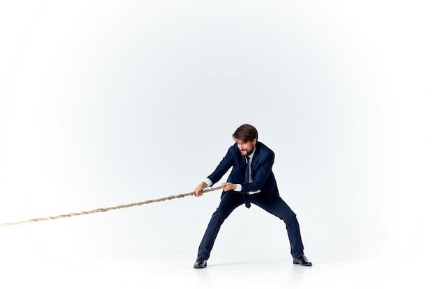 Hombre de negocios con una cuerda en sus manos sobre un modelo de tensión de fondo claro para lograr el objetivo