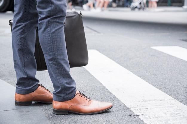 Hombre de negocios de cultivos de pie cerca de paso de peatones