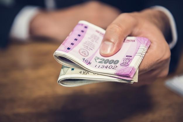 Hombre de negocios dando dinero en forma de rupias indias por los servicios prestados