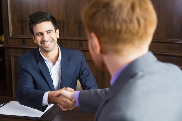 Hombre de negocios dándole la mano a otro hombre de negocios