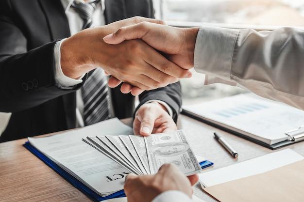 Hombre de negocios dándose la mano dando billetes de dólares al gerente de negocios