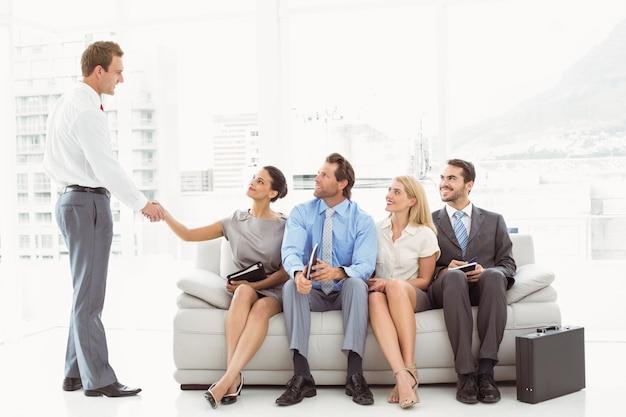 Hombre de negocios dándose la mano con la mujer además de personas esperando la entrevista