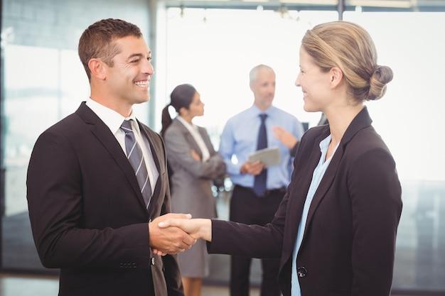 Hombre de negocios dándose la mano con mujer de negocios