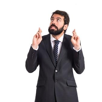 Hombre de negocios con los dedos cruzando sobre fondo blanco