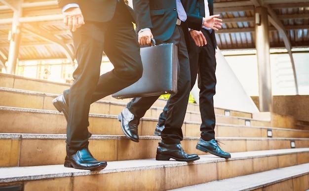 El hombre de negocios defocused o blured que camina las escaleras con el fondo de la ciudad, los hombres de negocios va al concepto del éxito, estilo del vintage.