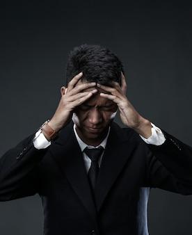 Hombre de negocios desesperado holding head. perder trabajo debido a la crisis global