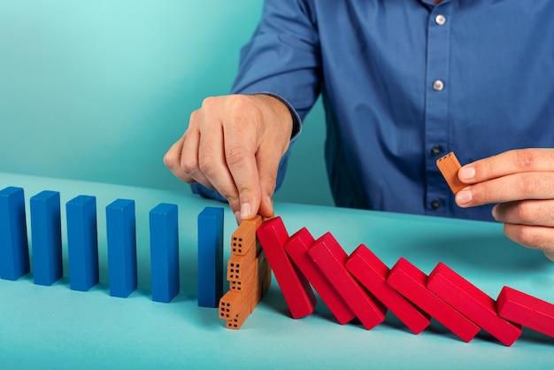 Hombre de negocios detiene la caída de una cadena como un juguete de dominó