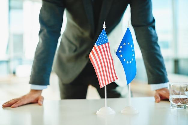 Hombre de negocios detrás de las banderas americana y europea
