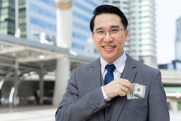 Hombre de negocios con dinero billetes de un dólar en la mano en el distrito de negocios