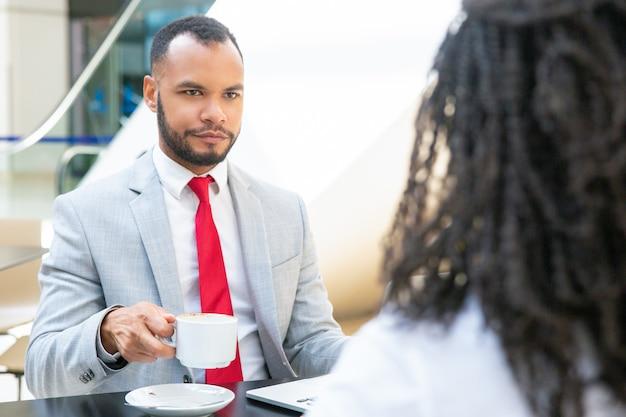 Hombre de negocios discutiendo trato con socio sobre taza de café
