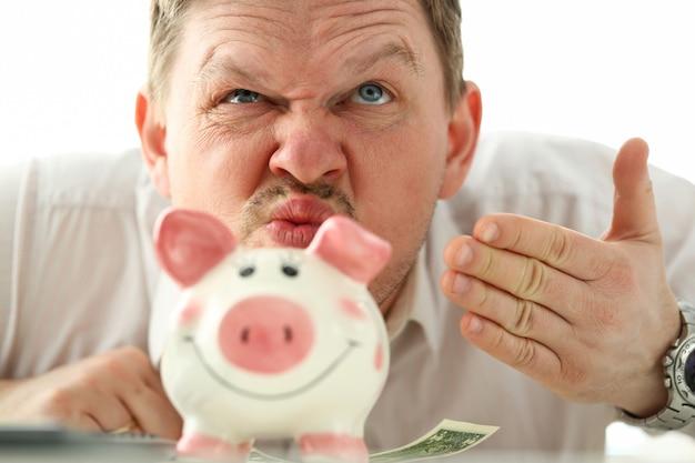 Hombre de negocios divertido que huele el aroma del dinero de piggybank