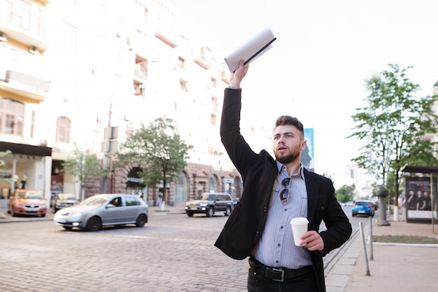 Hombre de negocios con documentos y una taza de café en sus manos coge un taxi cerca de la carretera.