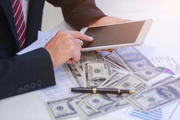 Hombre de negocios con los dólares de efectivo - concepto, tableta y finanzas del negocio.