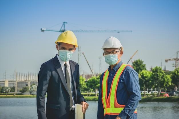 Hombre de negocios de dos personas hablando con senior en la construcción del sitio sobre proyecto de planta de bienes raíces y proyecto empresarial