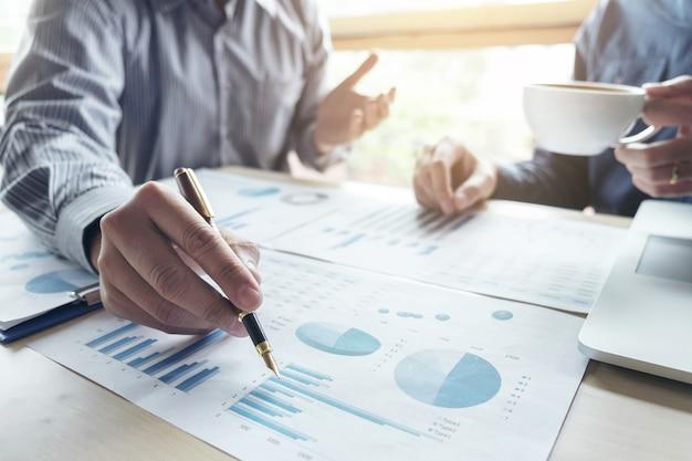 Hombre de negocios dos que trabaja la inversión financiera, escribiendo el informe analice el negocio y el mercado