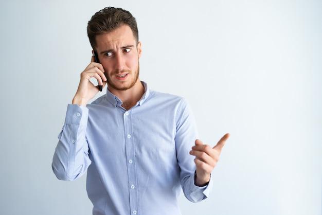 Hombre de negocios dudoso que señala el dedo lejos