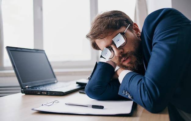 Hombre de negocios durmiendo en el trabajo con gafas con hojas de papel
