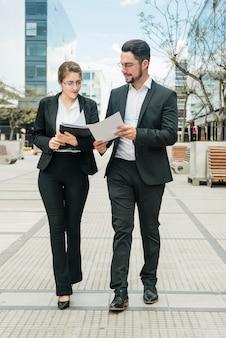 Hombre de negocios elegante y empresaria jovenes que miran el documento mientras que camina en el pavimento