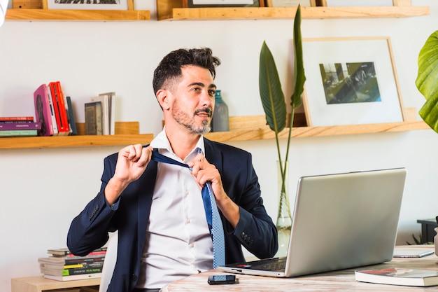 Hombre de negocios elegante con el ordenador portátil y el teléfono móvil en la tabla que pierde su lazo