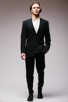 Hombre de negocios elegante en traje aislado en una pared blanca