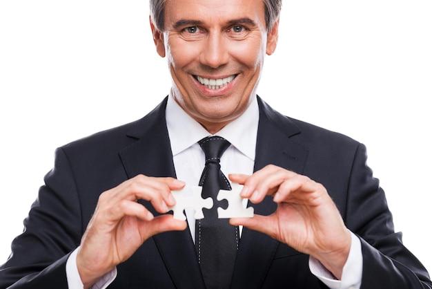 Hombre de negocios con elementos de rompecabezas. retrato de hombre maduro seguro en ropa formal sosteniendo dos elementos de rompecabezas y sonriendo mientras está de pie contra el fondo blanco.
