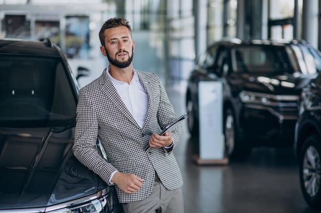 Hombre de negocios eligiendo un coche en una sala de exposición de coches